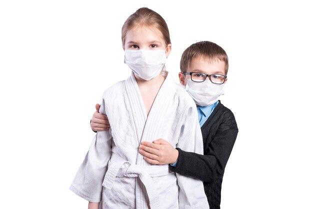 男の子の男子生徒は女の子のアスリートを抱きしめます。マスクされています。白い背景で隔離。高品質の写真