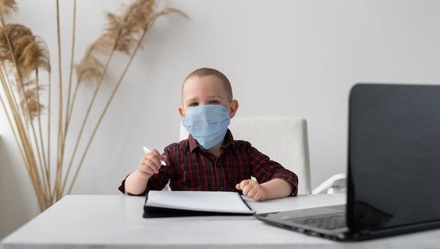 医療マスクの少年男子生徒はオンラインで宿題をします。彼の前にはラップトップがあります。テーブルの上にノートがあります。遠隔学習と検疫。インターネットで自宅で自習。