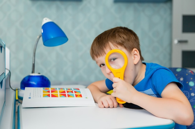 A boy schoolboy sits at a desk and learns a lesson. he holds a magnifying glass in his hand