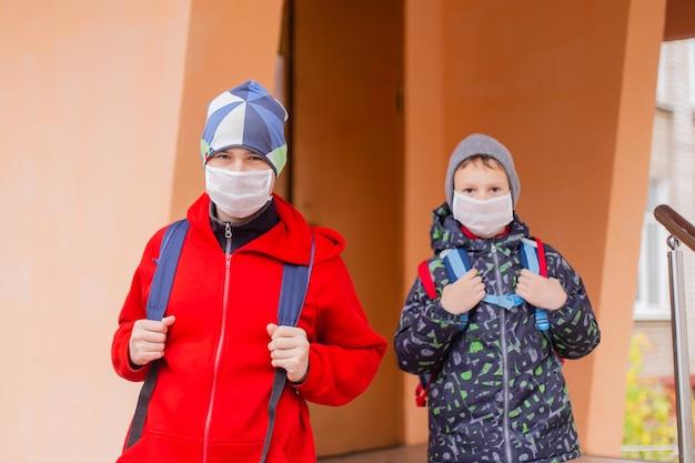 少年男子生徒は保護マスクを着用して学校を卒業します