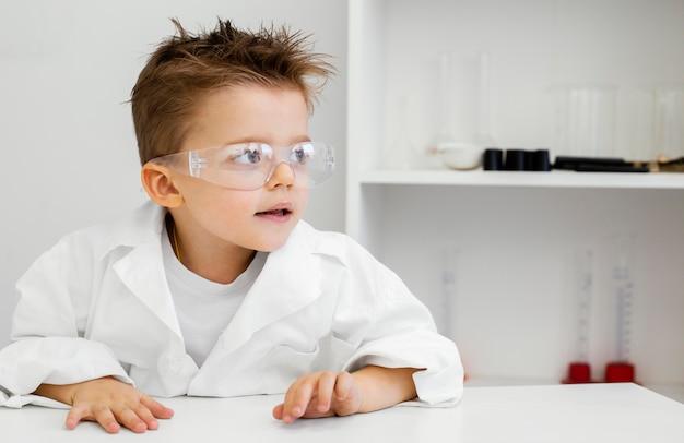 Ragazzo scienziato in laboratorio con occhiali di sicurezza