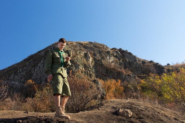 보이 스카우트 또는 레인저가 제복을 입고 나침반을 들고 산봉우리를 뒤에 두고 자신의 위치를 수정하기 위해 황야 트레일을 나갑니다.