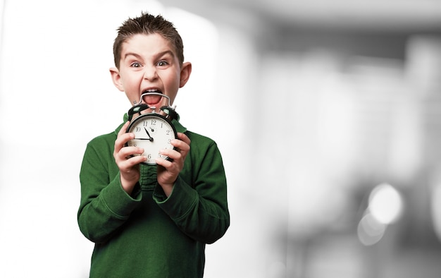 Boy screaming with an alarm clock