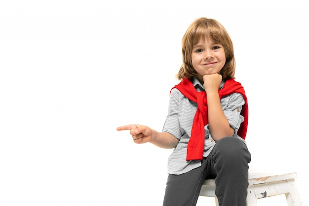A boy in a shirt and a jacket on his shoulders on a poor wall points his finger to the side on a white wall with blank space