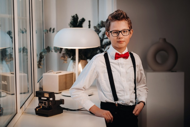 A boy in a shirt with a red bow tie and glasses stands at the window.