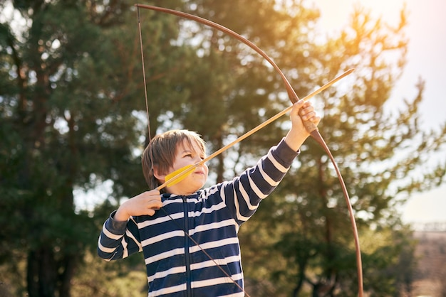 Boy shoots a bow in the open air