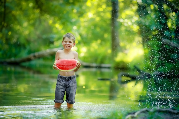 A boy in shorts and no shirt standing knee-deep in the forest river and eats a slice of red juicy watermelon
