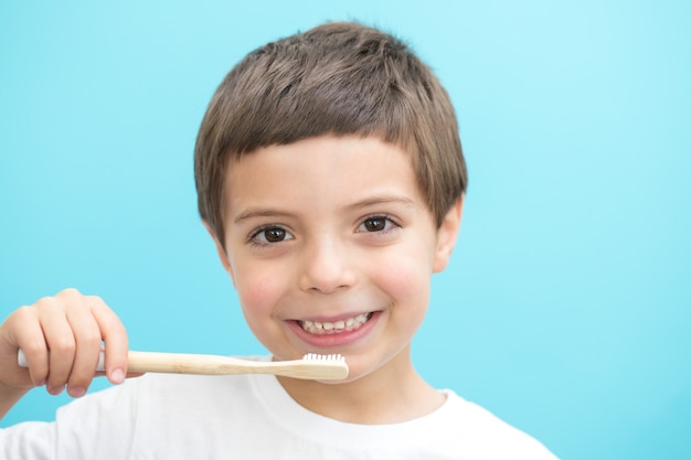 Boy show teeth with brush on blue background
