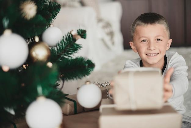 카메라에 크리스마스 선물을 보여주는 소년
