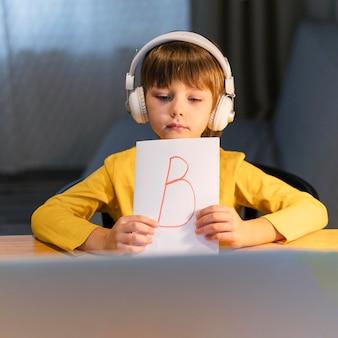 仮想コースで文字bの紙を示す少年