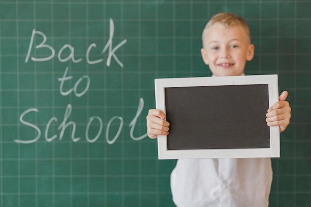 Boy showing blackboard in classroom