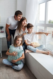 Boy showing something to his parents and sister from window