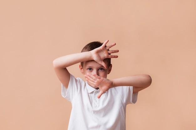 Мальчик показывает жест остановки, глядя на камеру на бежевом фоне