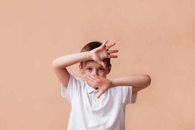 Boy showing stop gesture looking at camera on beige background