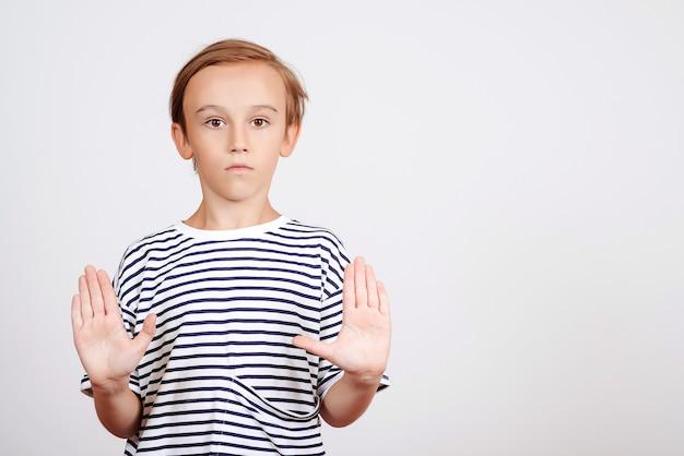 Мальчик показывает жест стоп с ладонью. детский студийный портрет. ребенок делает стоп-жест. знаки и символы.