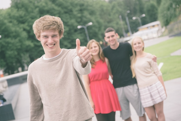 Boy showing thumbs up with friends
