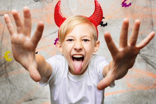 Boy shows funny faces for the camera on halloween