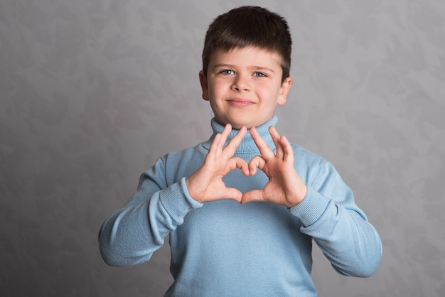 The boy shows his heart with his hands. the child made his hands in the shape of a heart. the baby gestures a symbol of love.