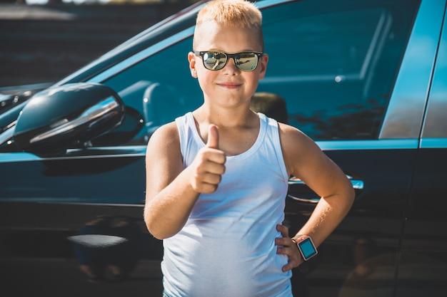 Мальчик показывает большой палец на фоне автомобиля