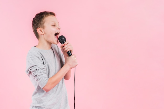 A boy singing song on microphone standing against pink backdrop