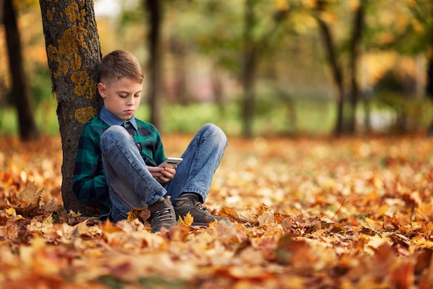 A boy sits in an autumn park under a tree with a phone in his hands