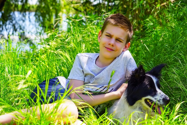 A boy sits on a green lawn and hugs a dog.