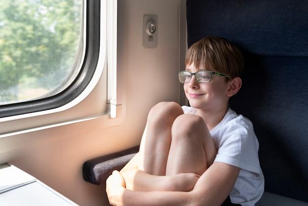 소년은 칸막이 마차에 앉아 무릎을 껴안습니다. 철도로 여행하십시오.