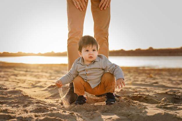 소년은 강둑의 모래에 아버지의 발에 앉아 있습니다.