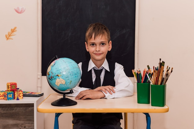 A boy sits at a school desk at a geography lesson