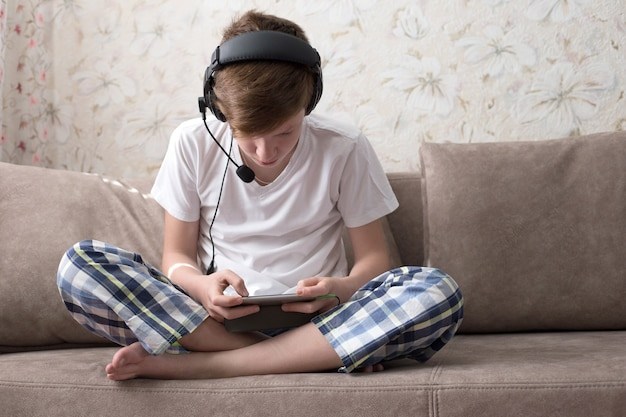 The boy sits on the sofa with headphones and plays video games on the phone
