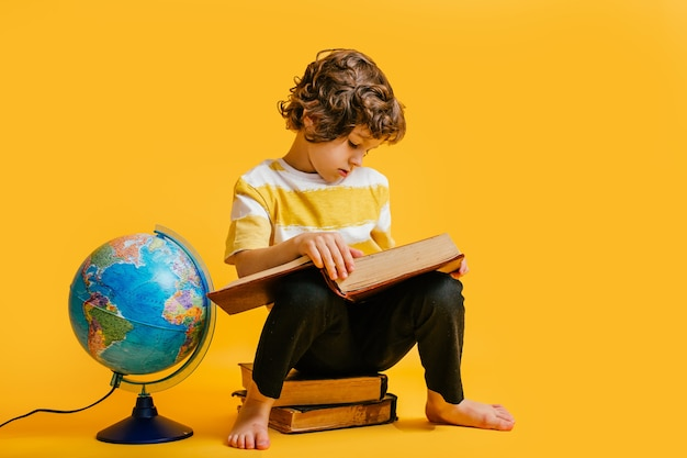 Boy sits on a stack of books, near to the globus