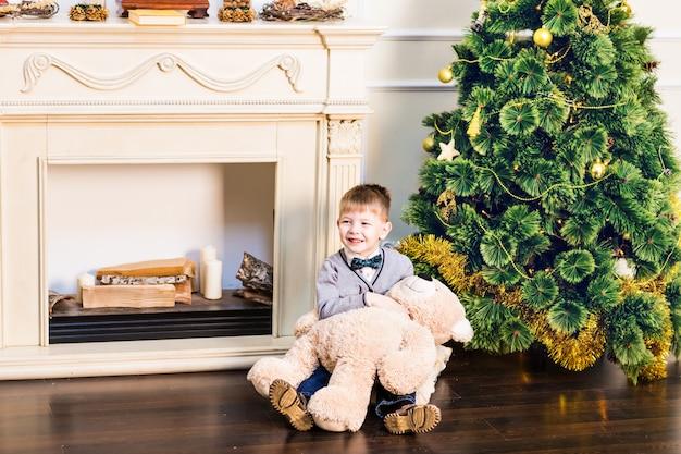 Мальчик сидит с мишкой и елки.