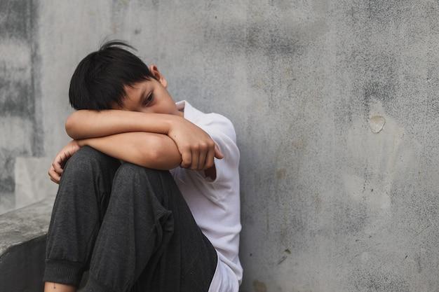 Мальчик сидит один после того, как пострадал от издевательств или жестокого обращения