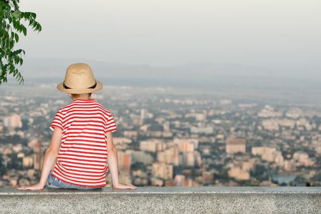 Мальчик сидит и смотрит на город с высоты. вид сзади, вечернее время