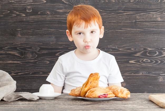 Мальчик сидит за столом с вкусной булочкой с начинкой из красной вишни, сладкой закуской, не диетической вредной пищей
