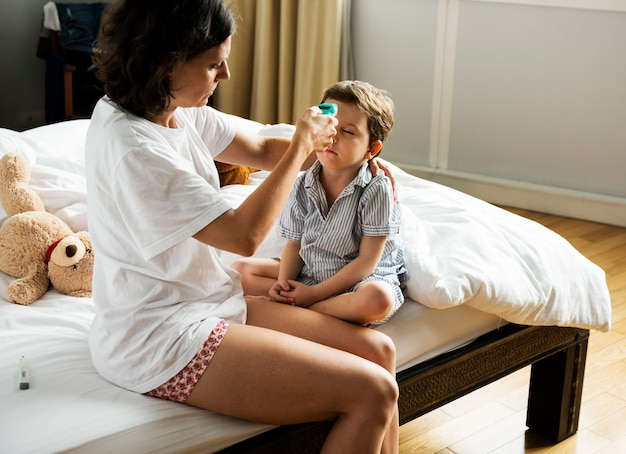 Boy sitting on the bed and his mom checking temperature