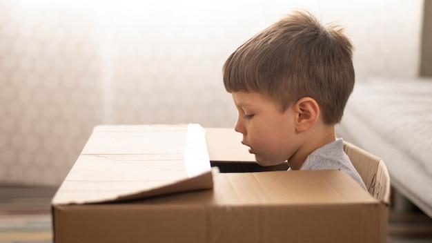 Boy sitting in cartoon box