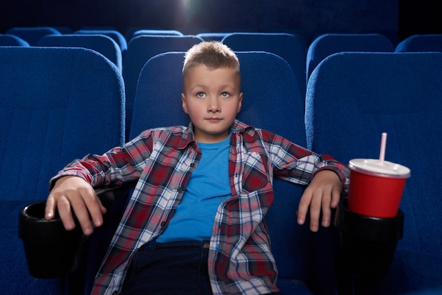 Boy sitting in cinema theatre, watching movie attentively.
