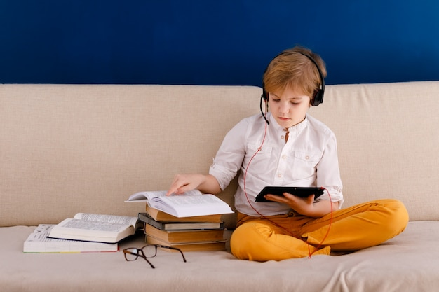 Boy sitting on the couch, eating pop corn and playing with gamepad during his online lesson at home, social distance during quarantine, self-isolation, online education concept