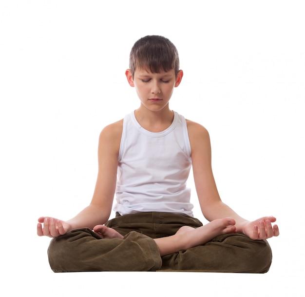 Boy sitting on floor meditating. yoga. lotus position.