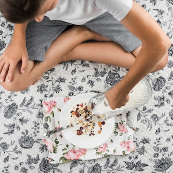 A boy sitting on floral carpet pouring milk in the oat flakes