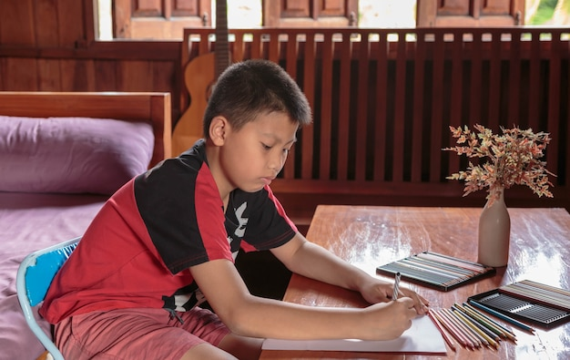 A boy sitting at his house drawing and painting.