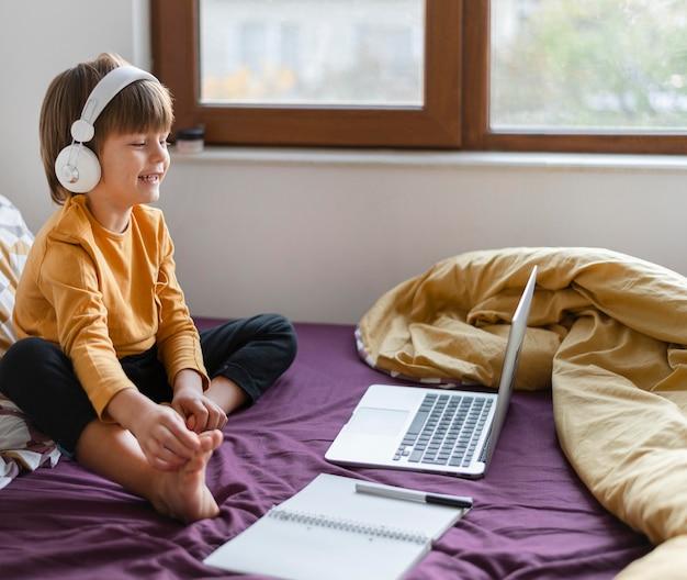 소년 침대에 앉아 헤드폰을 착용하는 동안 학습