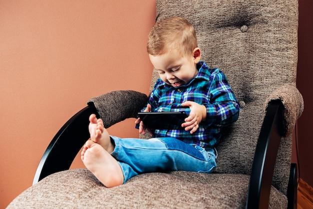 Мальчик сидит в постели и играет с мобильным телефоном