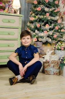 Мальчик сидит возле елки счастливый ребенок