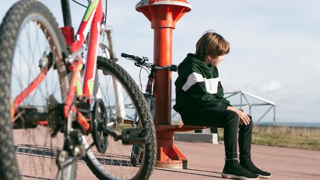그의 자전거와 함께 야외에서 망원경 옆에 앉아 소년