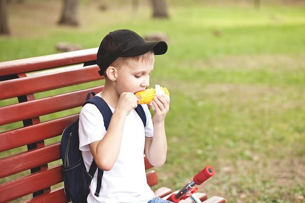 公園の屋外のベンチに座って、焼きたてのとうもろこしを食べている少年。