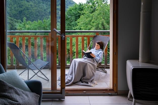 Мальчик сидит на шезлонге на террасе дома в горах во франции, читает книгу. ребенок накрыт одеялом, на улице. вид через окно