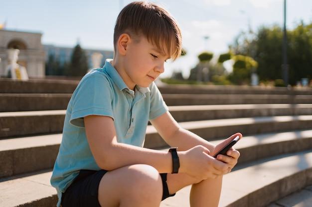 スマートフォンを手にして階段に座っている少年と面白い動画を見て緑のペニーボード