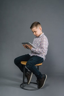 Boy sitting on stool looking at digital tablet against gray background